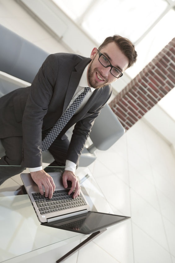 Portrait of young serious businessman working with laptop and document